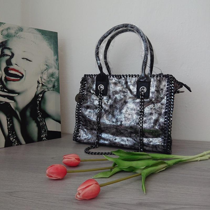 Strieborná retro dámska kabelka s čiernym podkladom a retiazkovou rúčkou.